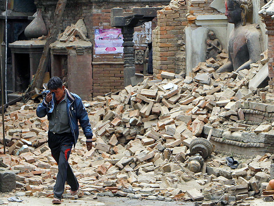 A Nepalese man cries as he walks through the earthquake debris in†Bhaktapur, near Kathmandu, Nepal, Sunday, April 26, 2015. A strong magnitude 7.8 earthquake shook Nepal's capital and the densely populated Kathmandu Valley before noon Saturday, causing extensive damage with toppled walls and collapsed buildings, officials said. (AP Photo/Niranjan Shrestha)